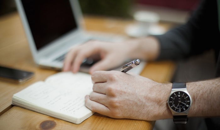 a man's arm writing in a notebook in front of a computer